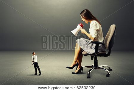 scared man going away from angry woman over dark background