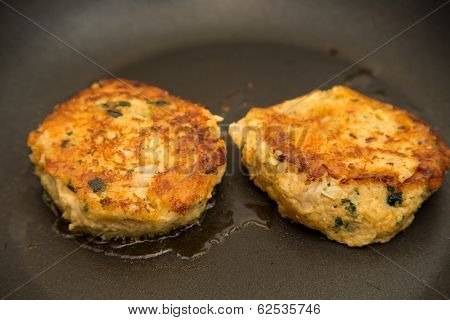 Two Crab Cakes Browning In Hot Oil