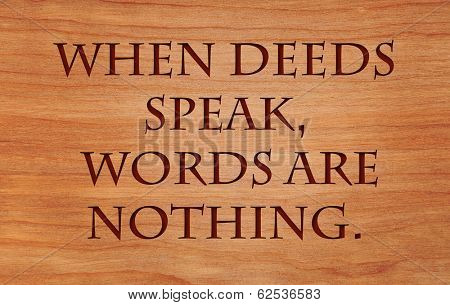 When deeds speak, words are nothing - motivational African Proverb on wooden red oak background