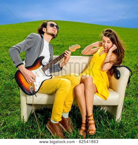 Man Playing Lovely Song To The Girl That Don't Like It On The Couch On The Green Field