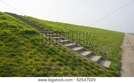 Stony stairs on a dike along a road