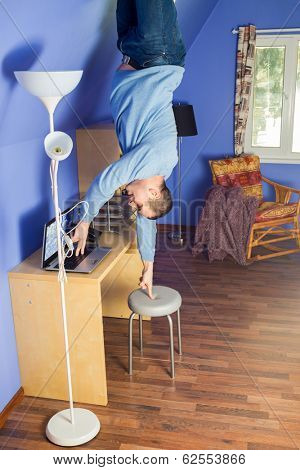 Man in jeans standing upside down under the table with computer