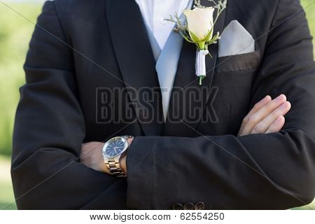 Midsection closeup of confident bridegroom with arms crossed