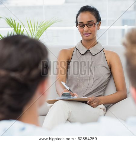 Therapist talking with couple on the couch and taking notes in therapists office