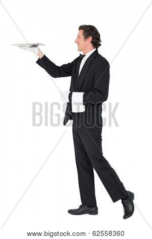 Full length of waiter carrying tray isolated over white background