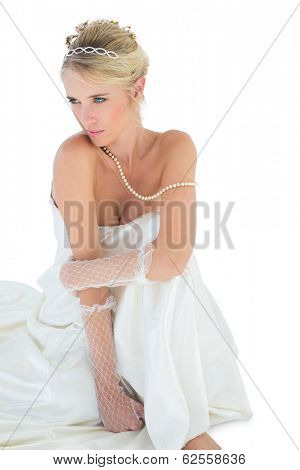 Thoughtful sensuous bride sitting over white background
