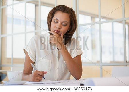 Concentrated young businesswoman working on blueprint in office