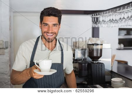 Portrait of a young smiling male barista holding cup of coffee at the caf�©