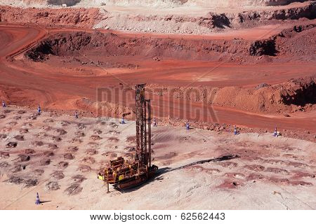 Large, open-pit iron ore mine showing the various layers of soil and iron rich ore