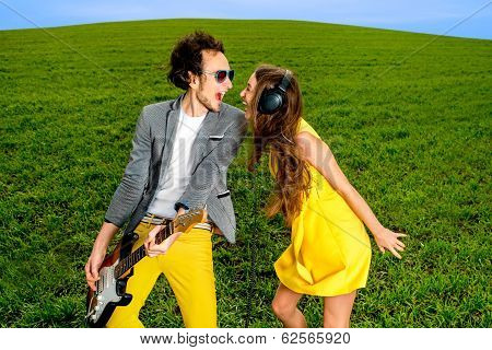 Young Couple Playing On Guitar And Enjoying The Music, They Shout And Sing On The Green Grass Backgr