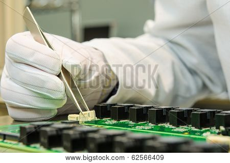 Female Hand Holding Tweezers And Installing Connector On Pcb