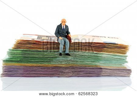symbolic photo for retirement and old age, figure of an old man sitting on a stack of bills