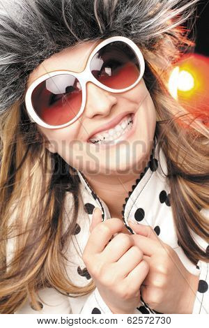 Beautiful and happy smiling woman with white sunglasses and hairy hat, dots jacket