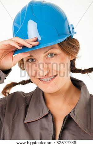 Close-up of  female worker with hardhat and braces smiling, studio on white