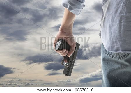 Man Holding Gun against an sky background