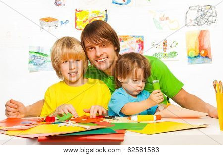 Little boys and father craft with glue