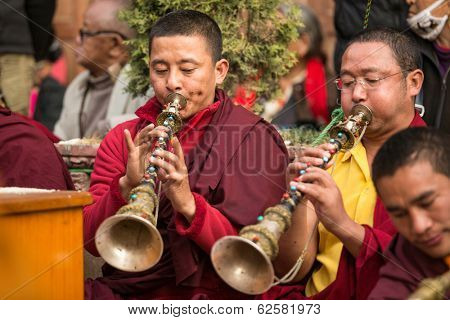 KHATMANDU, NEPAL - DEC 17, 2013: Unidentified tibetan Buddhist monks near stupa Boudhanath during festive Puja of H.H. Drubwang Padma Norbu Rinpoche's reincarnation's.