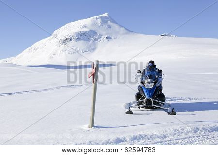 HEMAVAN, SWEDEN - MARCH 19. Snowmobile, driver along a trail on March 19, 2014 in Hemavan, Sweden.
