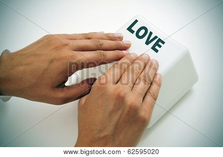 a man pressing a giant key with the word love written in it, depicting the idea of online dating or the need or search of love