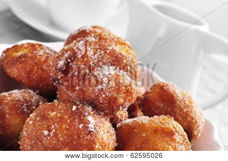 a plate with bunuelos de viento, typical pastries of Spain eaten in Lent, on a set table