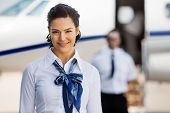 foto of cabin crew  - Portrait of pretty stewardesses smiling with pilot and private jet in background at airport terminal - JPG