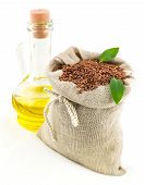foto of flax seed  - Macro view of flax seeds in flax sack with leaves and glass bottle of flax oil isolated on white background - JPG