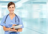 image of medicare  - Beautiful smiling doctor woman over blue hospital background - JPG