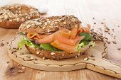 stock photo of bagel  - Salmon whole grain bagel on wooden kitchen board on wooden background - JPG