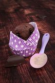 stock photo of mixture  - Chocolate cupcake in purple dotted paper baking form chocolate bar and baking mixture on wooden background - JPG