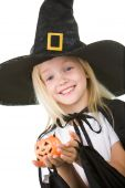 stock photo of antichrist  - Portrait of girl in witch costume and small pumpkin in hands looking at camera - JPG
