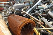 stock photo of scrap-iron  - piles of scrap iron with broken and rusted objects in a special waste landfill - JPG
