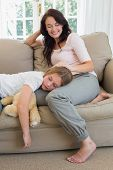 Loving mother looking at daughter sleeping on her lap in living room