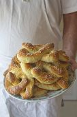 foto of pretzels  - A chef holds out a plate piled high with freshly baked Philadelphia Soft Pretzels - JPG