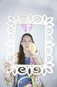 Beautiful young woman wearing rabbit ears and posing with frame and Easter egg