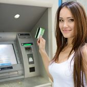 pic of plastic money  - Young woman withdrawing money from credit card at ATM - JPG