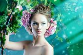 image of nymph  - Beautiful young woman standing under an arch of flowers and overgrown loach - JPG