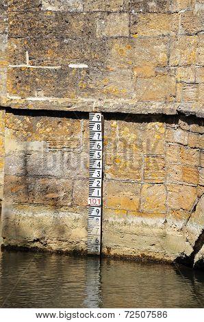 Depth marker on stone bridge.