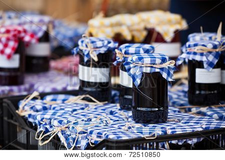 Many Preserving Jars With Dark Jam In A Market