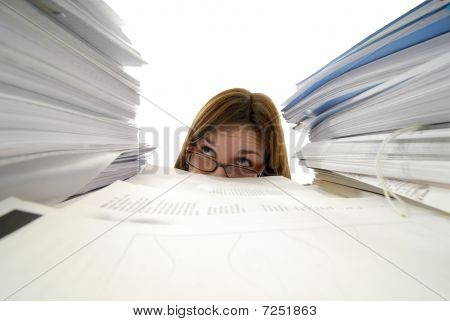 Young Woman With Glasses Looking Up From Behind Stacks Of Paper