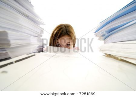 Young Woman Looking From Behind A Stack Of Papers