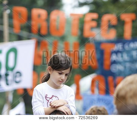 Little girl with sign in background