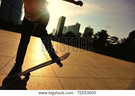 woman skateboarder skateboarding at sunrise city