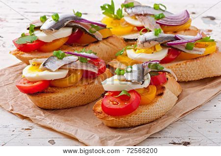Crostini with anchovies, tomatoes and egg, decorated with greens