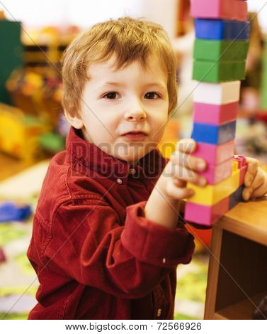 portrait of little cute boy making towel with lego
