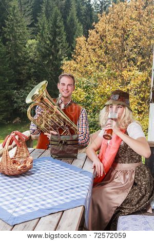 Young couple in traditional Bavarian clothes enjoy your leisure in common