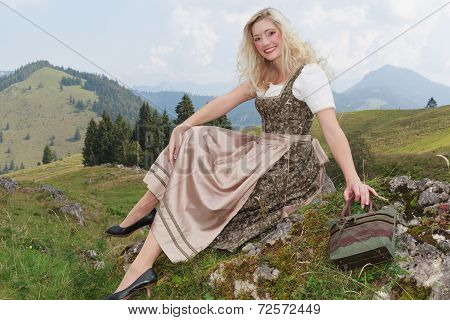 Young woman in dirndl, sitting on a rock