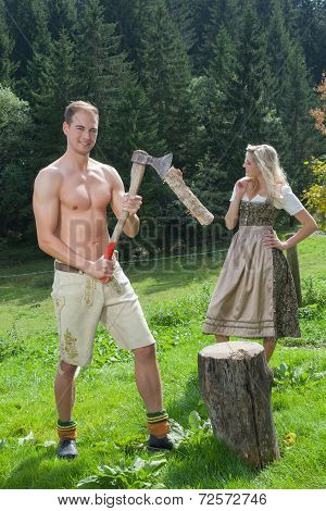 Scene of a Bavarian couple in traditional costumes chopping wood