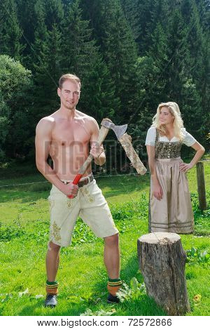 Bavarian couple in love chopping wood in fashionable dress clothing