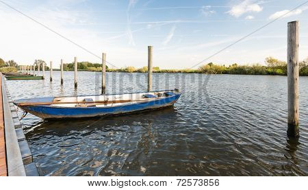 Moored Iron Rowing Boat In Rippling Water