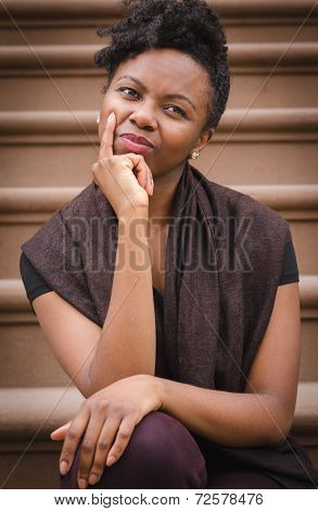 Young black lady sitting on step thinking